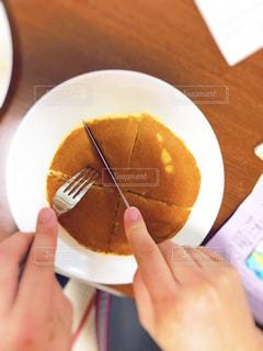 朝食のホットケーキを切ってくれる主人の手の写真・画像素材[1215704]
