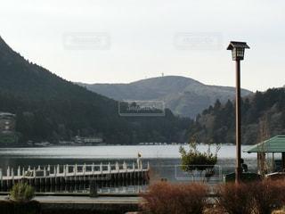 背景の山が付いている水の体の上の橋の写真・画像素材[814250]