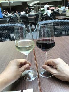 ワインのグラスとテーブルに座っている男の人の写真・画像素材[728817]