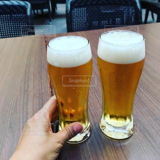 テーブルにビールのグラスを持っている手の写真・画像素材[737492]