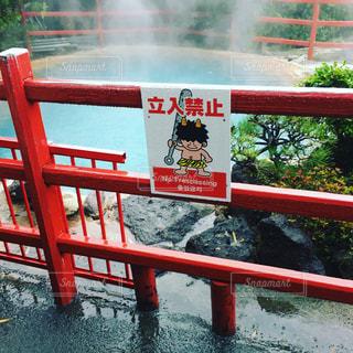 フェンスの横に座っている赤いベンチの写真・画像素材[841409]