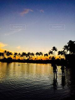 水の体の横に立っている人のグループの写真・画像素材[718359]