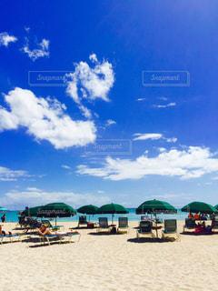 曇りの日にビーチ パラソルに座っている人々 のグループ - No.718381