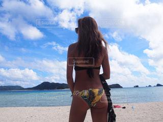 水の体の近くのビーチに立っている女性の写真・画像素材[714781]