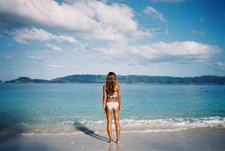 水の体の近くのビーチに立っている人の写真・画像素材[865217]