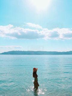 水の体の横に立っている人の写真・画像素材[962306]