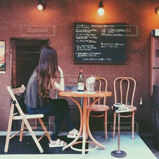 レストランのテーブルに座っている女性 - No.728470