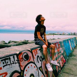 水の体の近くのビーチに座っている男 - No.815889