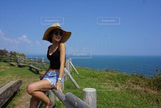 水の体の横にあるベンチに座っている女性 - No.783149