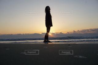 バック グラウンドで夕焼けのビーチに立っている人の写真・画像素材[849500]