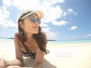 水の体に座っているサングラスの女の写真・画像素材[1139317]
