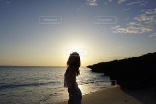 水の体の近くのビーチに立っている人 - No.1139323