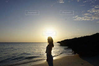 水の体の近くのビーチに立っている人の写真・画像素材[1139325]