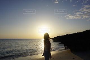 水の体の近くのビーチに立っている人の写真・画像素材[1139326]
