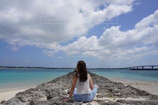 水の体の近くのビーチに立っている人の写真・画像素材[1139335]