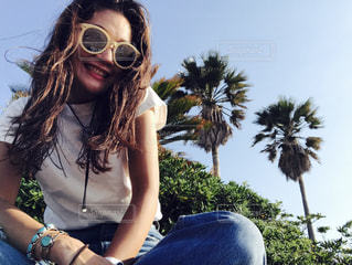 晴れた日に座っているサングラスを身に着けている女性の写真・画像素材[1141869]