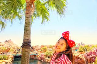 ヤシの木の前に立っている女の子の写真・画像素材[1239610]