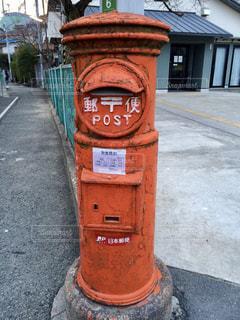 建物の側に座っている赤い消火栓の写真・画像素材[1280235]