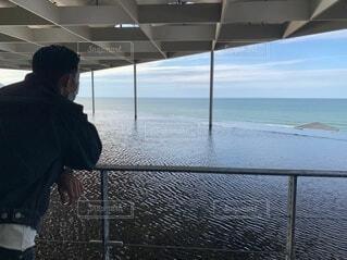 水の体の隣に立っている男の写真・画像素材[3936729]