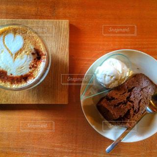 木製テーブルの上の皿にケーキ - No.1066482