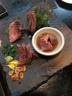 木製のテーブルの上に肉刺しのプレートの写真・画像素材[1013558]
