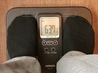 体重計に乗った中年男、ただ今63.7kgの写真・画像素材[1274002]