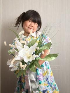 花瓶のあるテーブルに座っているライザ・メイ・ディゾンの写真・画像素材[2503001]