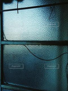 青みがかった光が透ける窓ガラスの写真・画像素材[2116392]