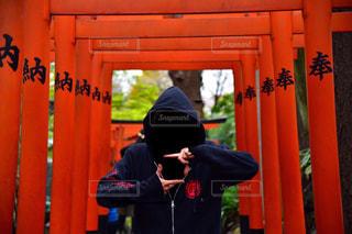 フェンスの前に立っている男の写真・画像素材[919587]
