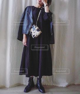カーテンの前に立っている青いドレスを着た人の写真・画像素材[3131620]