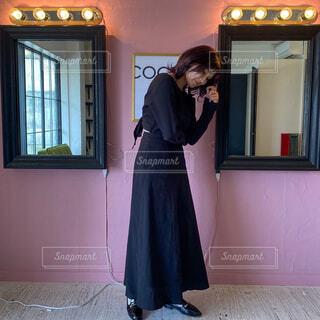 携帯電話で話している窓の前に立っている女性の写真・画像素材[4531874]