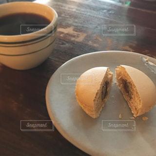 コーヒー カップの横にある皿の上のケーキの一部の写真・画像素材[986081]