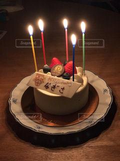 火のついたキャンドルのバースデーケーキの写真・画像素材[2220220]