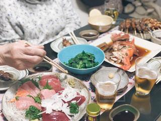 食品のプレートをテーブルに座っている人々 のグループの写真・画像素材[1078118]