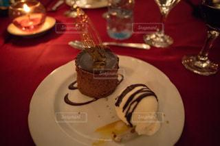 テーブルの上のケーキをのせた白プレートの写真・画像素材[1130119]