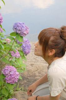 花の前に座っている女性の写真・画像素材[1226520]