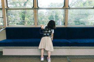 車内の窓際に立っている女の子の写真・画像素材[1880758]