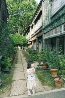 家の前に立っている女の子の写真・画像素材[1881997]