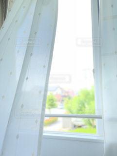 風に揺れる窓辺のカーテンの写真・画像素材[1425209]