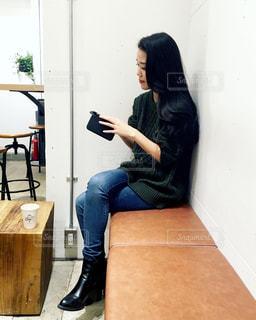 携帯電話で話している椅子に座っている女性の写真・画像素材[1029601]