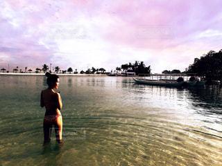海に入って夕日を眺める私の写真・画像素材[1031212]