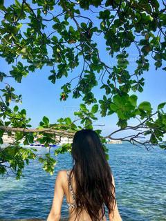 水の体の横に立っている女性の写真・画像素材[1111179]