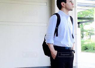 横向きに立っている白シャツの男の写真・画像素材[713707]