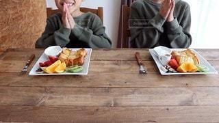 食べ物を食べるテーブルに座っている人の写真・画像素材[3141668]
