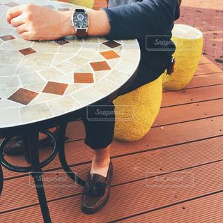 テーブルに手を置き、椅子に座っている男性の写真・画像素材[762808]