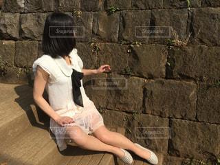石の壁の上に座って人の写真・画像素材[1069109]