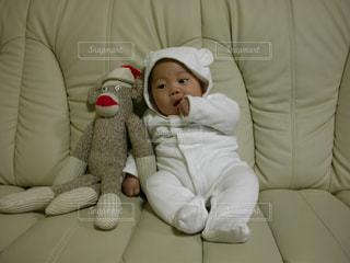 サルのぬいぐるみの横にいる赤ちゃんの写真・画像素材[736380]