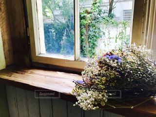 窓の前で花と花瓶の写真・画像素材[1464031]
