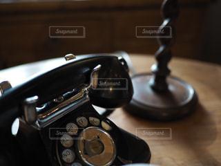 テーブルの上の黒電話の写真・画像素材[1103996]