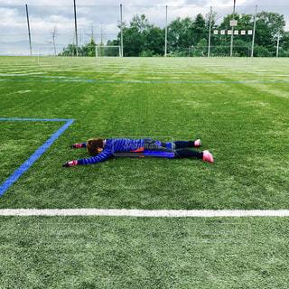 サッカーのフィールドに横になっている少女 - No.854027